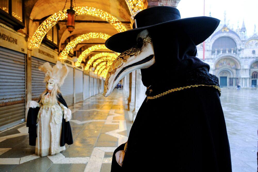 Le persone indossano maschere e costumi da carnevale in Piazza San Marco a Venezia, Italia, il 7 febbraio 2021