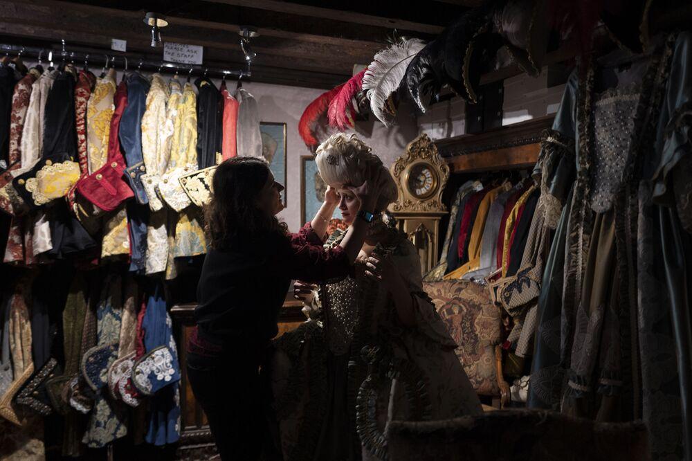 Una dipendente aiuta una festaiola a indossare una parrucca e un costume da carnevale tradizionale nel negozio La Bauta a Venezia il 6 febbraio 2021