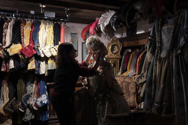 Una dipendente aiuta una festaiola a indossare una parrucca e un costume da carnevale tradizionale nel negozio La Bauta a Venezia il 6 febbraio 2021 - Sputnik Italia