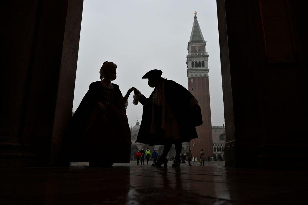 Le persone che indossano costumi da carnevale sfilano in Piazza San Marco a Venezia il 6 febbraio 2021, nonostante il carnevale sia stato annullato a causa della pandemia Covid-19