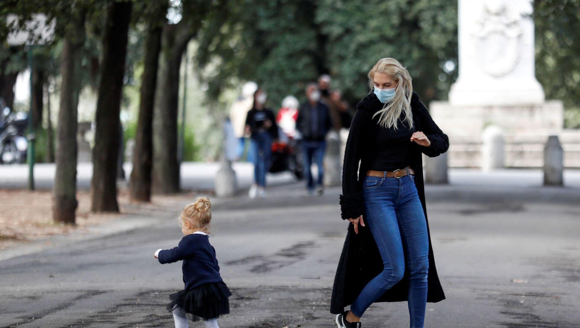 Covid-19, una donna con una bambina a Roma, Italia - Sputnik Italia, 1920, 15.02.2021