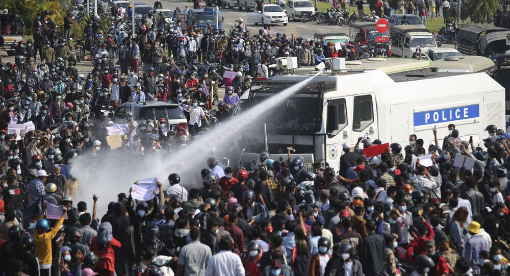 A police truck sprays water to a crowd of protesters in Naypyitaw, Myanmar on Monday, Feb. 8, 2021.