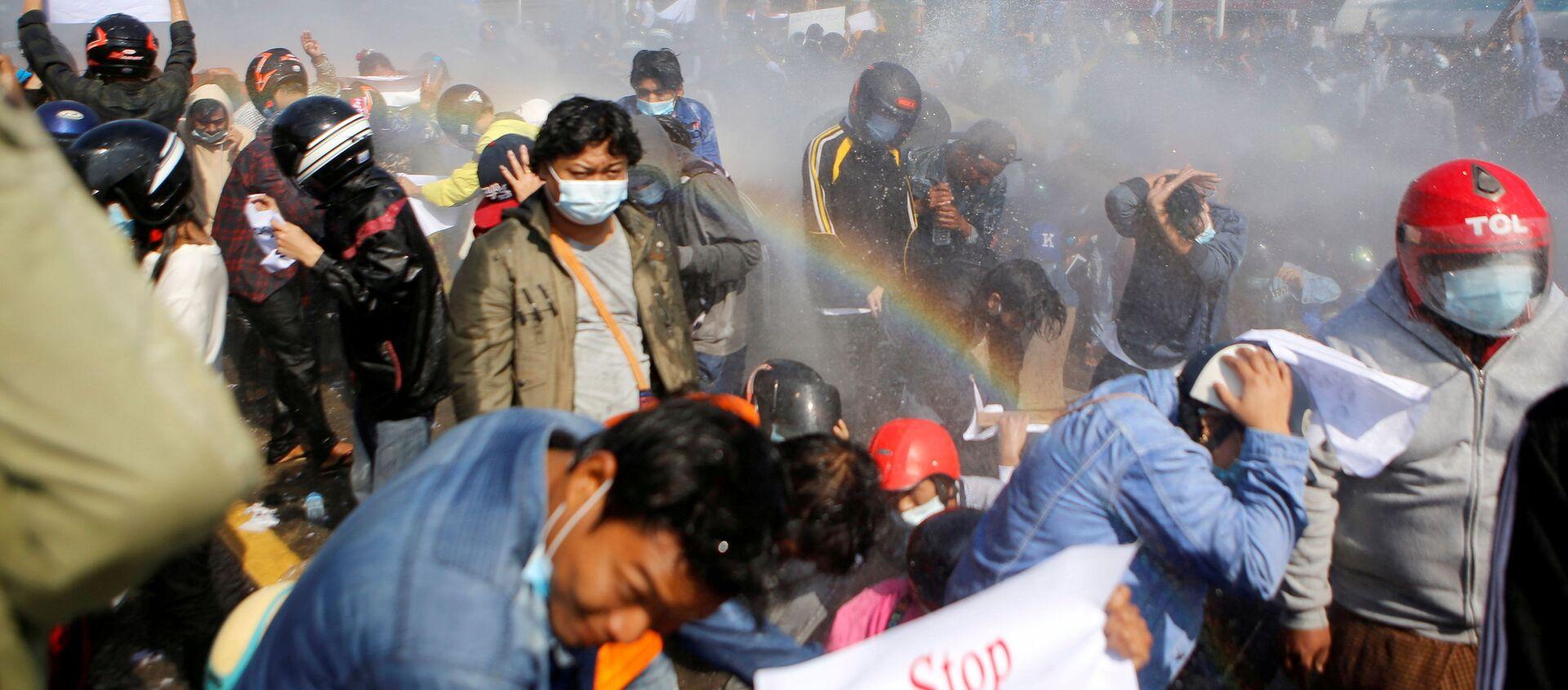 Полиция стреляет из водомета по демонстрантам, выступающим против военного переворота, в Нейпьито, Мьянма - Sputnik Italia, 1920, 22.02.2021