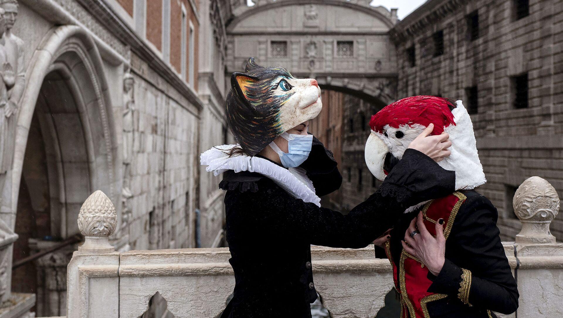 Венецианцы в карнавальных масках и костюмах у Моста Вздохов в Венеции - Sputnik Italia, 1920, 15.02.2021