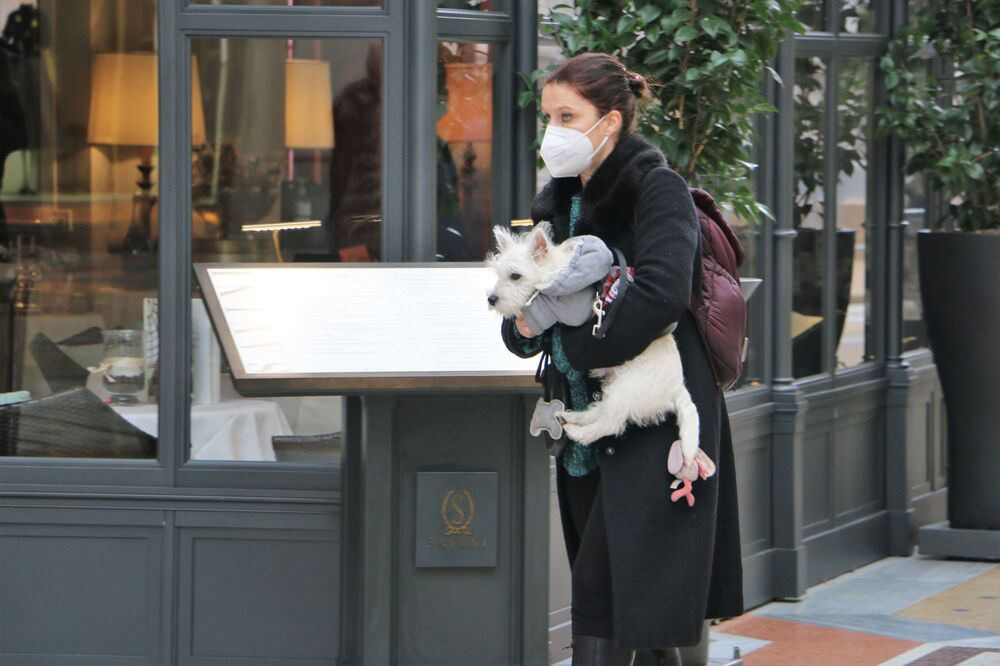 Una donna in una mascherina protettiva con un cane a Milano