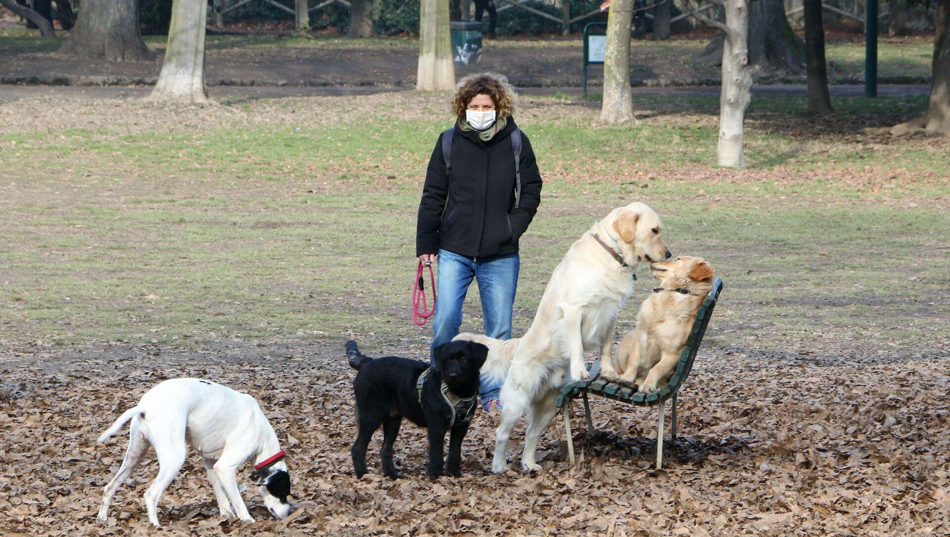Una donna con i cani in un parco di Milano, Italia - Sputnik Italia, 1920, 10.03.2021
