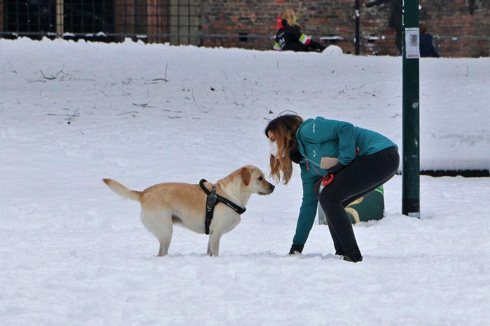 Una donna gioca con un cane in un parco di Milano, Italia