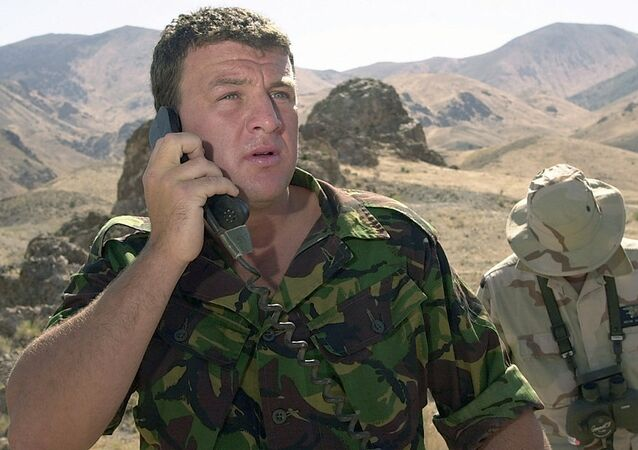 A British Special Forces member from the 22nd Special Air Service (SAS) at Hereford, England, uses a DR IX phone system to relay exact target area information to F-18D aircraft personnel.