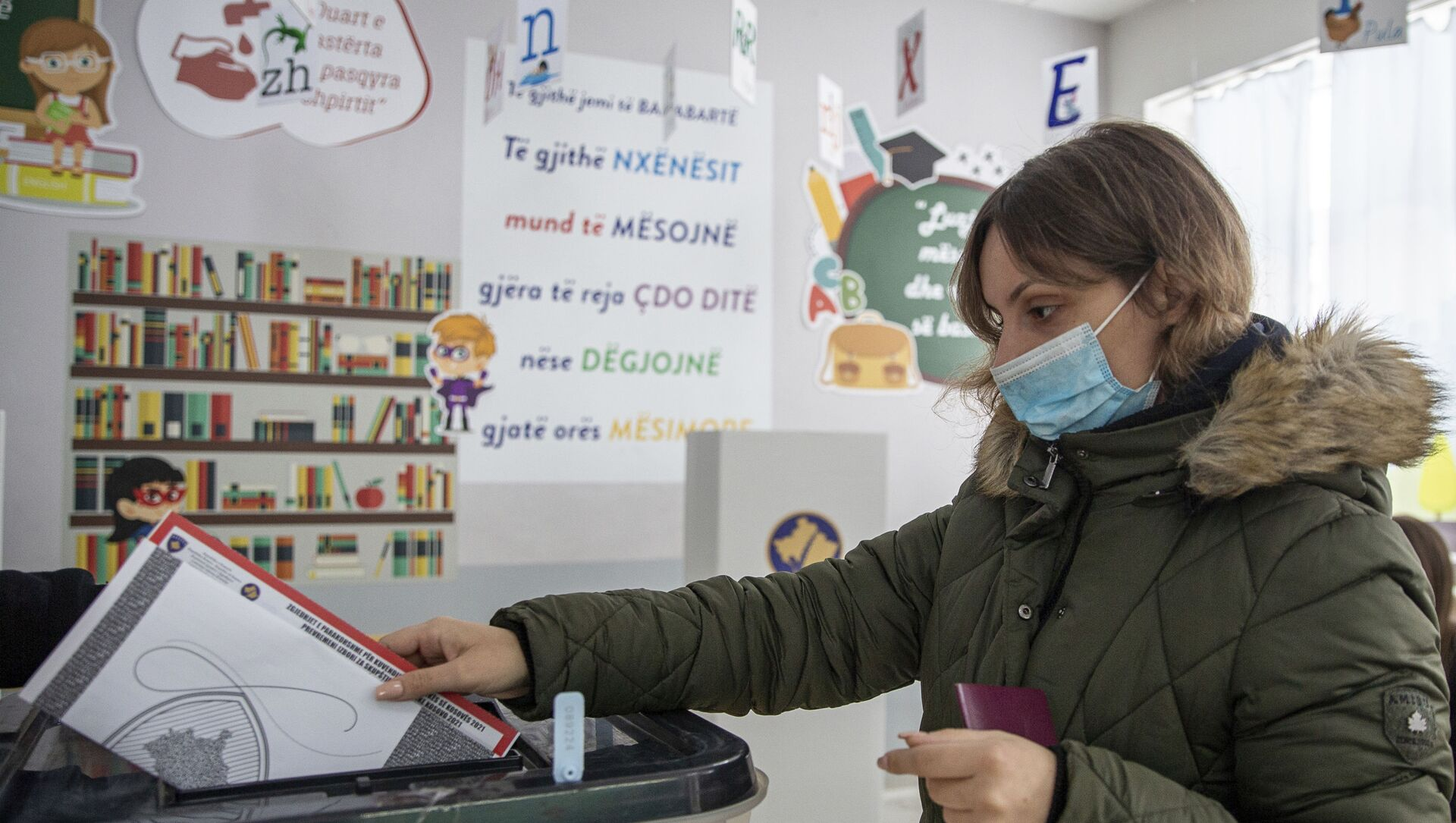 A woman wearing a protective mask casts her vote in parliamentary elections in capital Pristina, Kosovo, Sunday, Feb. 14, 2021. Kosovo is holding an early parliamentary election to form a new government amid the coronavirus pandemic, an economic downturn and stalled negotiations with wartime foe Serbia.  - Sputnik Italia, 1920, 14.02.2021