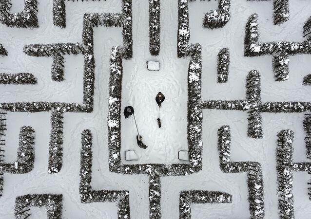 Passanti con cani nel mezzo di un labirinto coperto di neve a Gelsenkirchen, in Germania