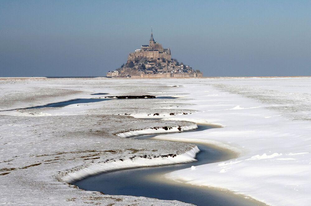 La baia innevata di Mont Saint-Michel nella regione occidentale francese della Normandia, Francia, il 10 febbraio 2021