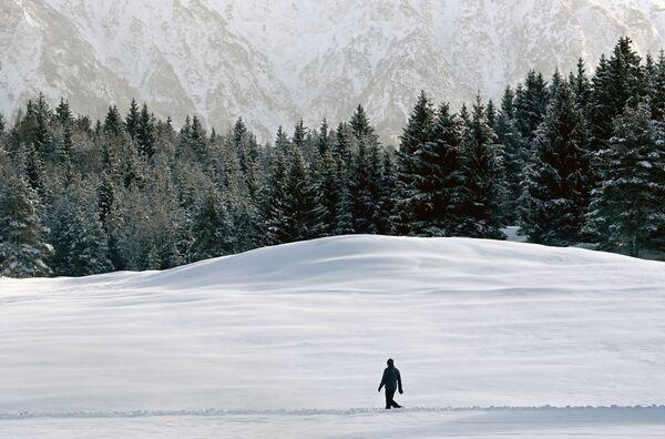 Un uomo cammina attraverso il paesaggio innevato vicino al villaggio bavarese di Kaltenbrunn vicino a Garmisch-Partenkirchen, nella Germania meridionale, il 13 gennaio 2021 - Sputnik Italia