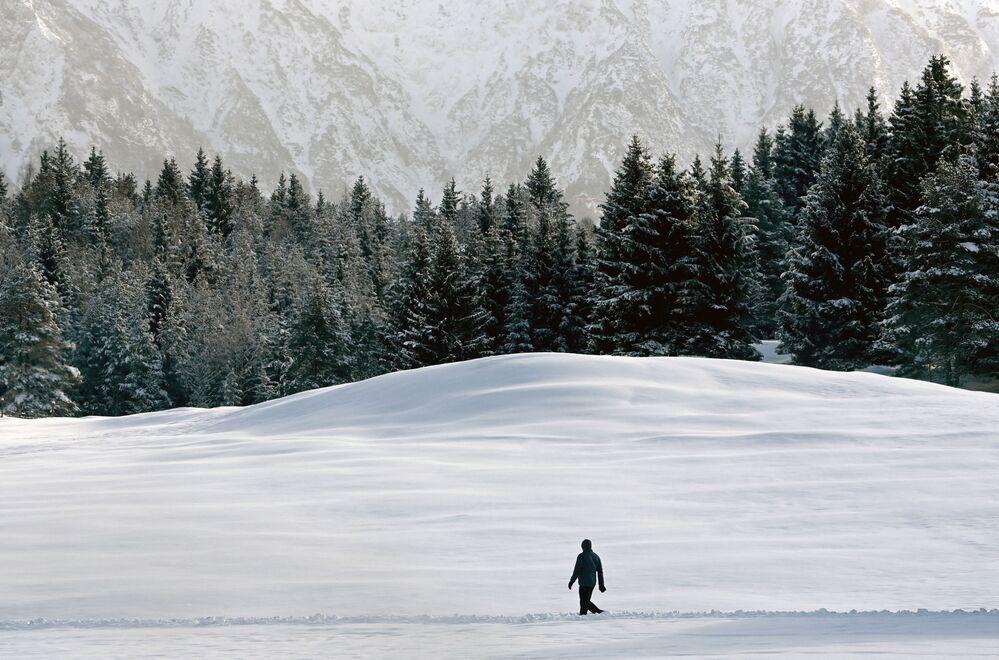 Un uomo cammina attraverso il paesaggio innevato vicino al villaggio bavarese di Kaltenbrunn vicino a Garmisch-Partenkirchen, nella Germania meridionale, il 13 gennaio 2021
