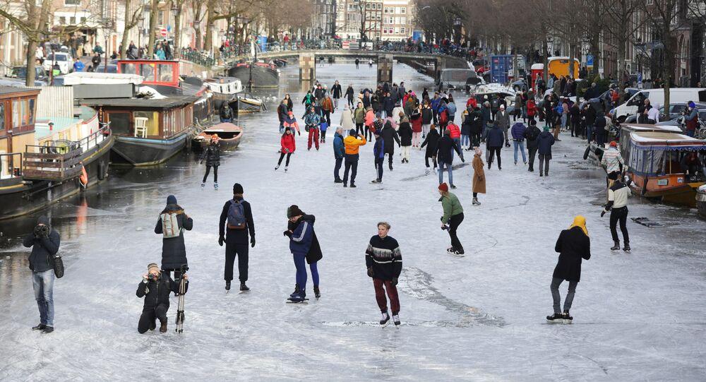 La gente pattina sul canale ghiacciato di Amsterdam