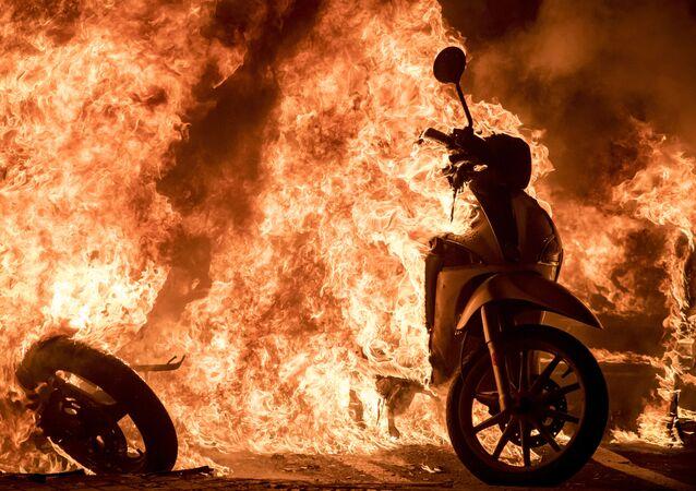 Scooter in fiamme in una delle strade di Barcellona, dove si sta svolgendo una manifestazione di protesta a sostegno del rapper Pablo Hasel