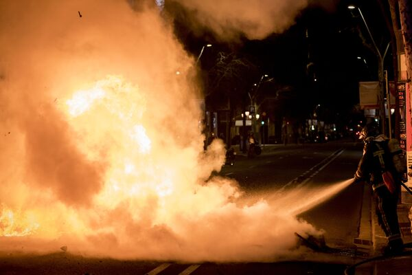 Un vigile del fuoco spegne uno scooter in fiamme in una strada di Barcellona, dove si sta svolgendo una manifestazione di protesta a sostegno del rapper Pablo Hasel - Sputnik Italia
