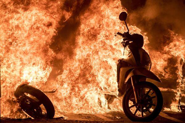 Scooter in fiamme in una delle strade di Barcellona, dove si sta svolgendo una manifestazione di protesta a sostegno del rapper Pablo Hasel - Sputnik Italia