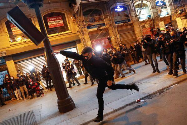 Un manifestante lancia un cestino durante una protesta dei sostenitori del rapper Pablo Hasel a Madrid, Spagna - Sputnik Italia