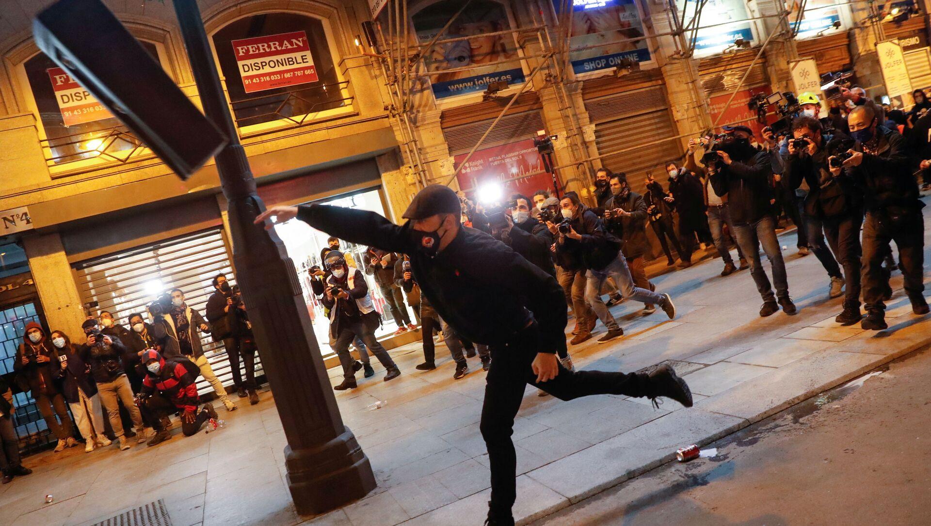 Демонстрант бросает мусорное ведро во время протеста сторонников рэпера Пабло Хазеля в Мадриде, Испания - Sputnik Italia, 1920, 20.02.2021