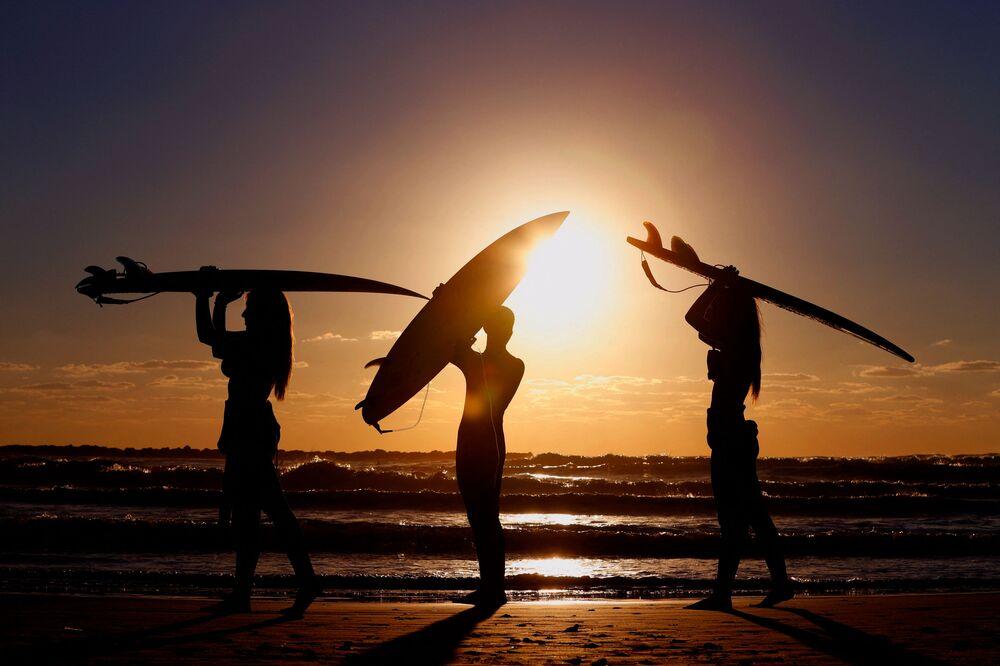 Surfisti israeliani sulla costa nei pressi della città di Netanya al tramonto.