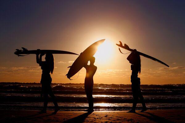 Surfisti israeliani sulla costa nei pressi della città di Netanya al tramonto.  - Sputnik Italia