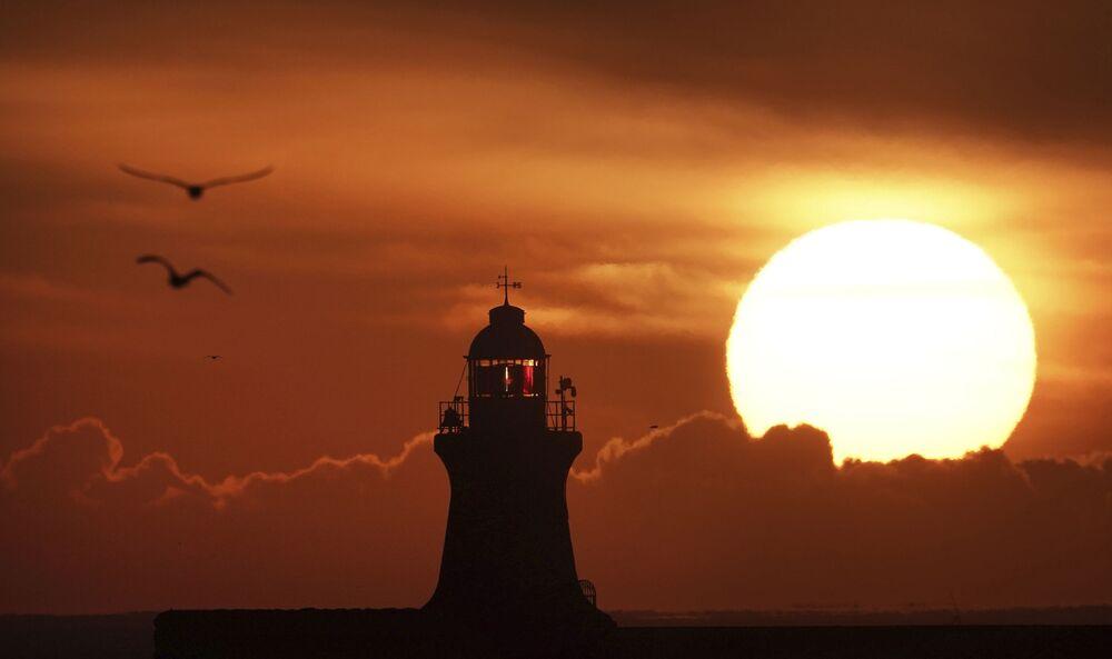 Il sole sorge sul faro di South Shields sulla costa nord-orientale dell'Inghilterra.