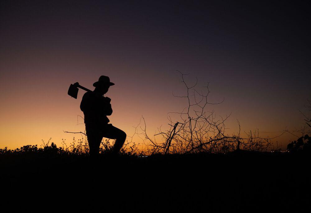 Il profilo di un contadino palestinese che impugna una zappa sullo sfondo di un tramonto a est di Gaza City.