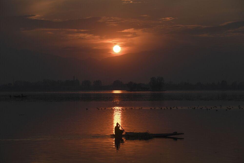 Un uomo in una barca al tramonto sul lago di Dal a Srinagar, India.