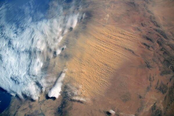 Una gigantesca tempesta di sabbia proveniente dal deserto del Sahara, la foto scattata dal cosmonauta russo Sergej Kud'-Sverčkov dalla ISS.  - Sputnik Italia