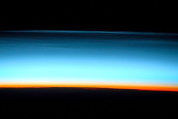 Le nubi nottilucenti, la foto scattata dal cosmonauta russo Sergey Kud-Sverchkov dalla ISS.  - Sputnik Italia