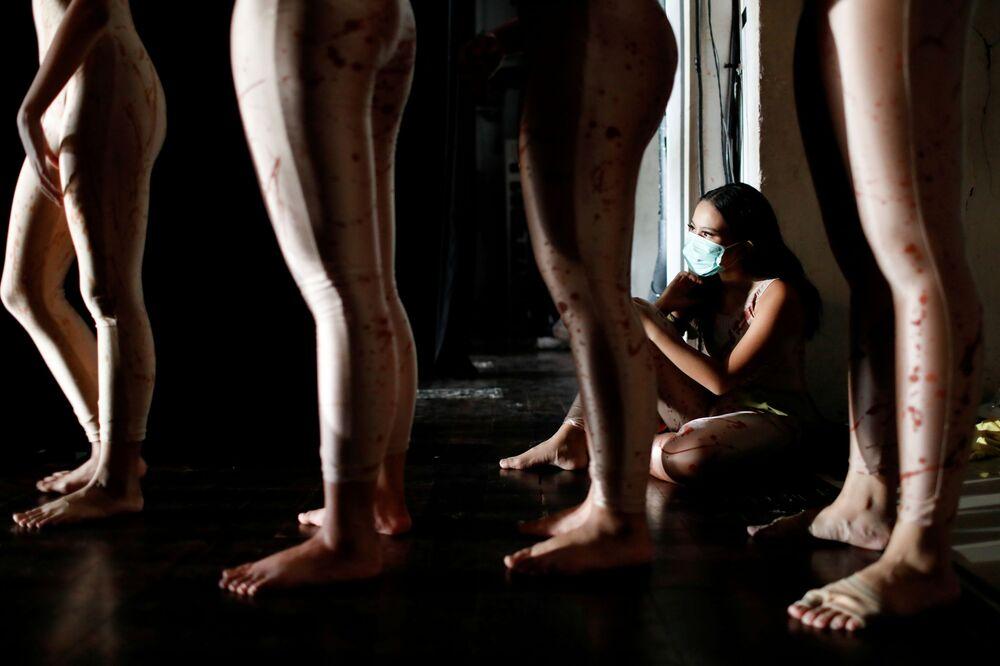 Una ragazza balla in maschera protettiva mentre si esibisce alla Casa delle arti in Indonesia