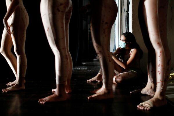 Una ragazza balla in maschera protettiva mentre si esibisce alla Casa delle arti in Indonesia - Sputnik Italia