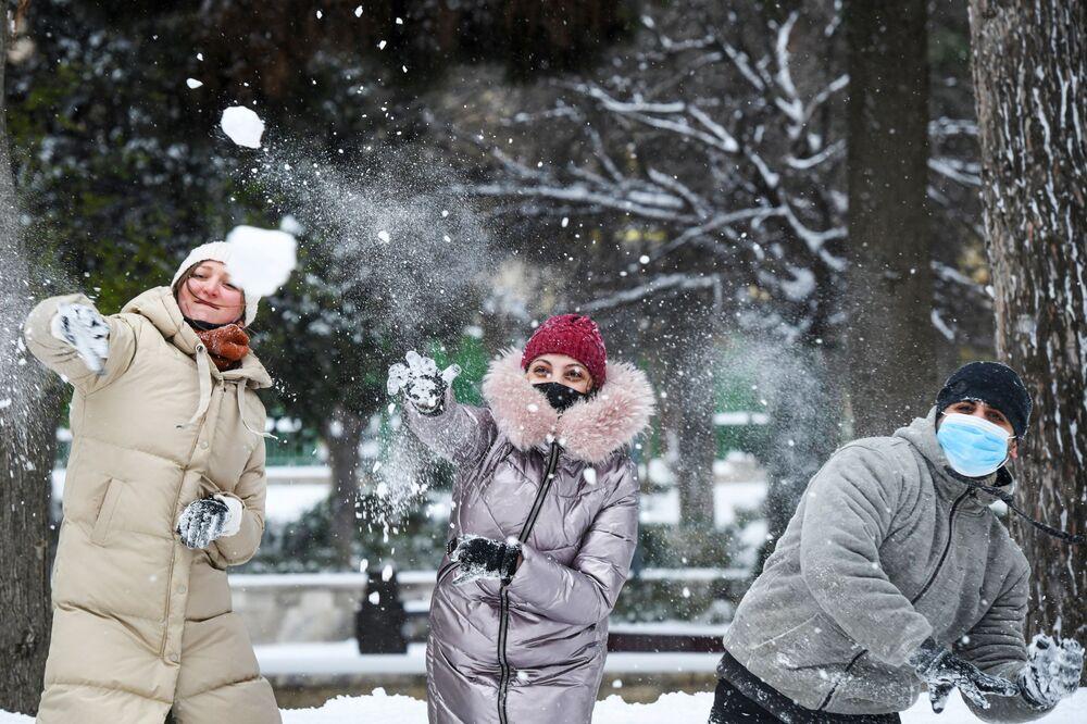 La gente gioca a palle di neve su una strada di Baku durante la nevicata