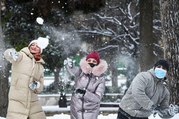 La gente gioca a palle di neve su una strada di Baku durante la nevicata - Sputnik Italia