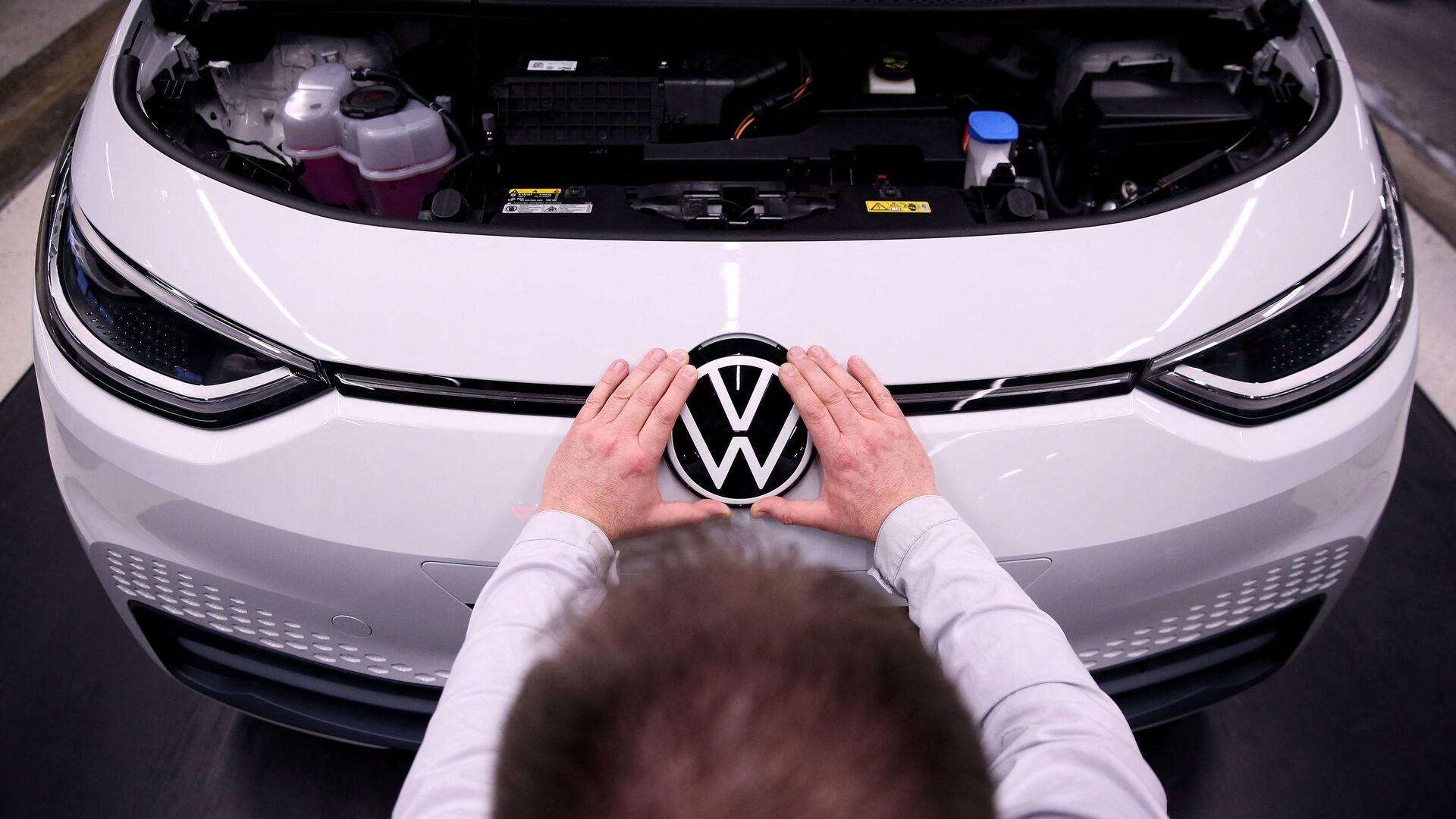 Рабочий устанавливает логотип VW на электромобиле Volkswagen ID.3 на сборочном конвейере автозавода Volkswagen - Sputnik Italia, 1920, 03.09.2021