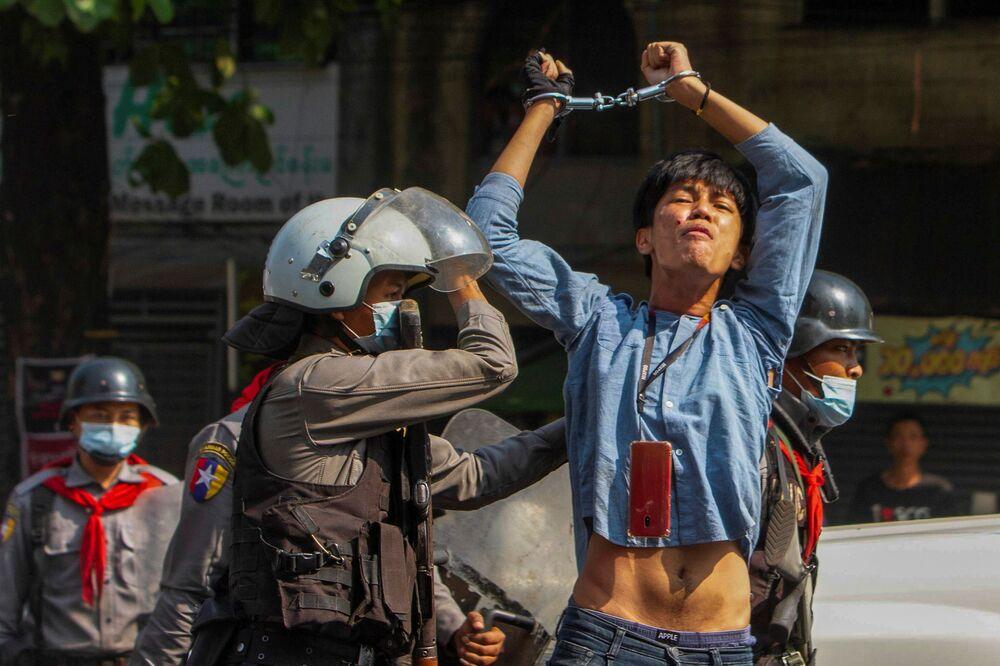 Un protestante arrestato da agenti di polizia durante una manifestazione contro un colpo di stato militare a Yangon, Myanmar