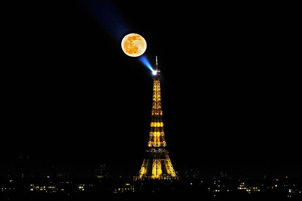 La luna gibbosa calante appare nel cielo dopo la Luna piena di neve sopra la Torre Eiffel a Parigi, il 28 febbraio 2021