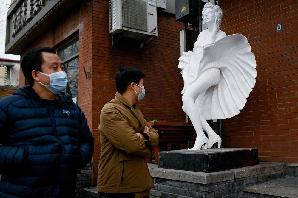 Un uomo guarda una statua di Marilyn Monroe fuori da un negozio a Pechino, il 2 marzo 2021