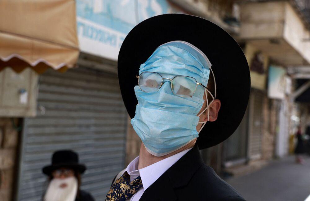 Un uomo che indossa le mascherine protettive sul viso durante le celebrazioni del Purim a Gerusalemme