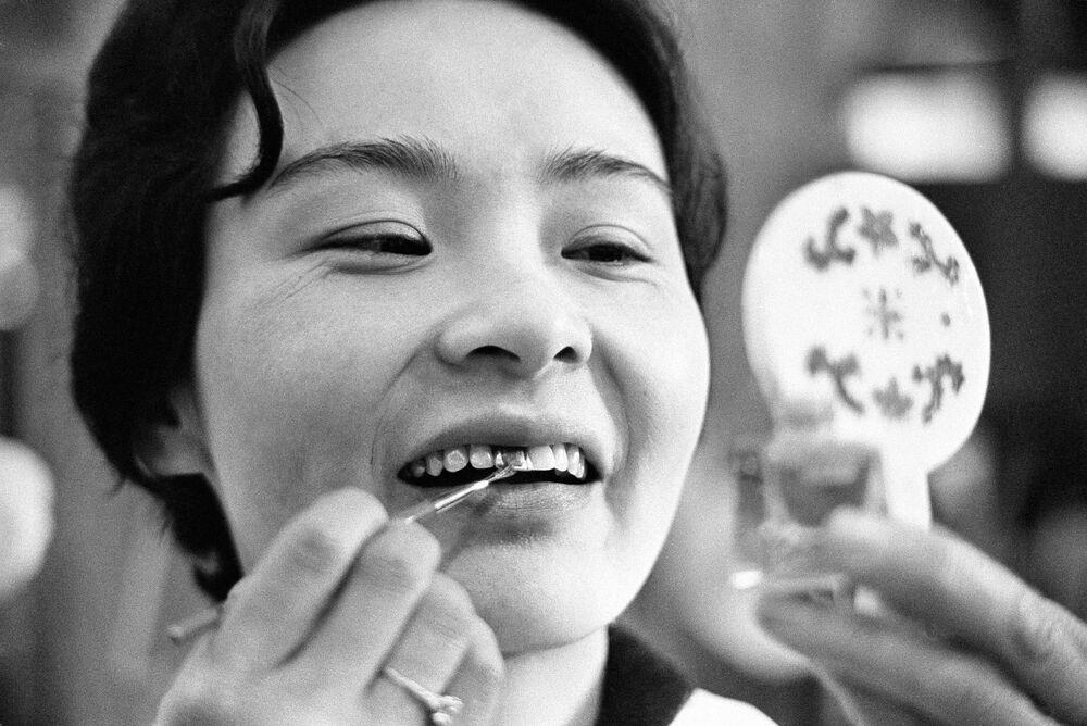 I denti delle donne in Giappone sono stati distinti in base al colore in tempi diversi.  Nei tempi antichi, le donne si coprivano i denti con vernice nera come segno di bellezza.  Successivamente divenne un'usanza solo per le donne sposate.  Toshiko Fukayam applica un rivestimento colorato ai suoi denti, 7 aprile 1966, Giappone