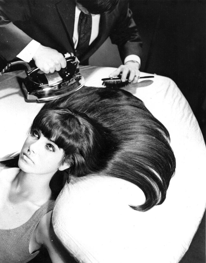 Il prototipo delle moderne piastre per capelli.  Il parrucchiere pettina e accarezza i capelli della modella su un asse da stiro.  La tavola è progettata per adattarsi al contorno della testa e consentire ai capelli di aprirsi a ventaglio.  20 ottobre 1965, New York