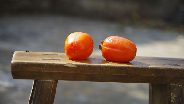 Две спелых хурмы лежат на скамейке - Sputnik Italia