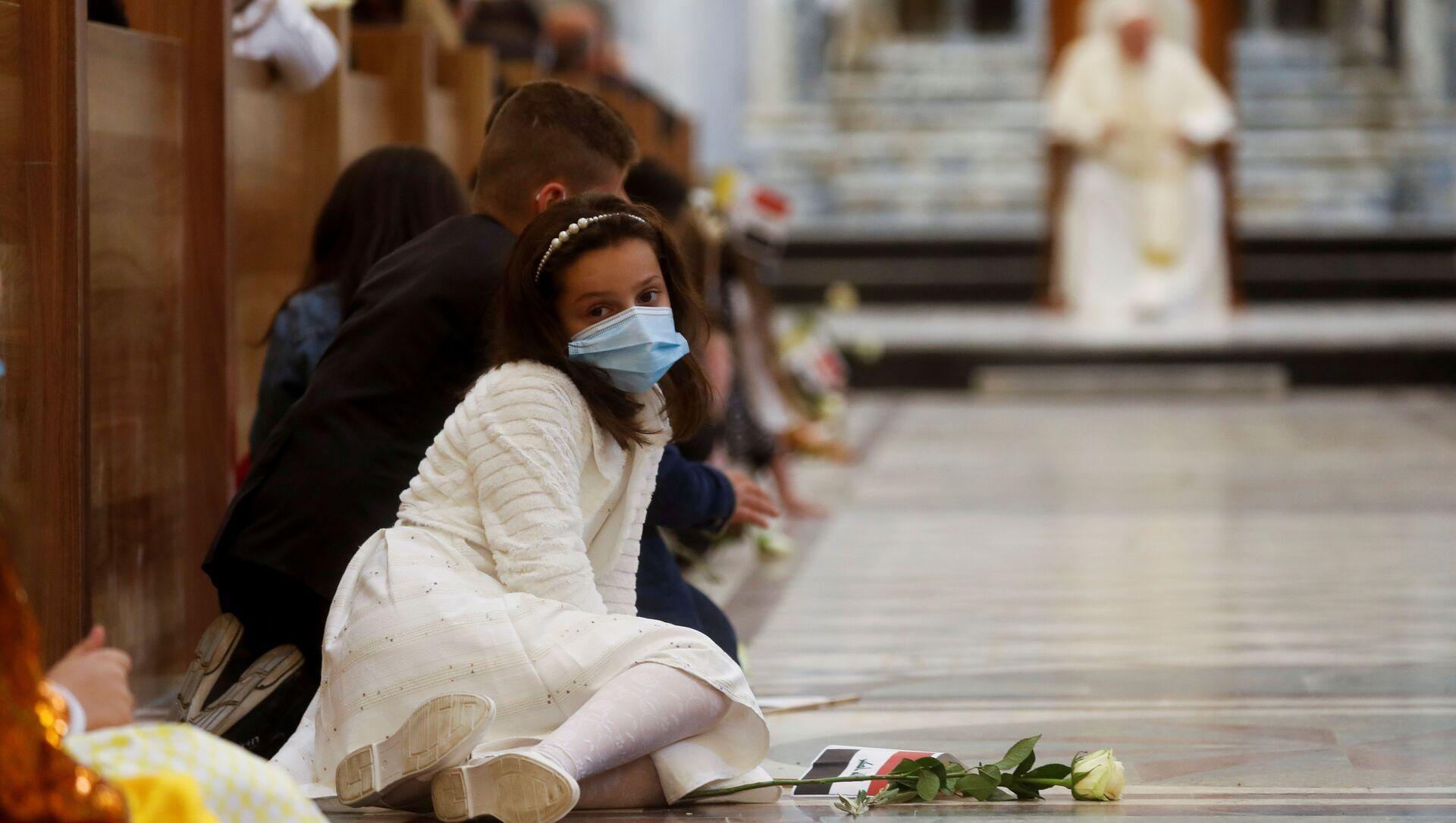 Una ragazza sul pavimento della chiesa mentre Papa Francesco dice la messa - Sputnik Italia, 1920, 07.03.2021