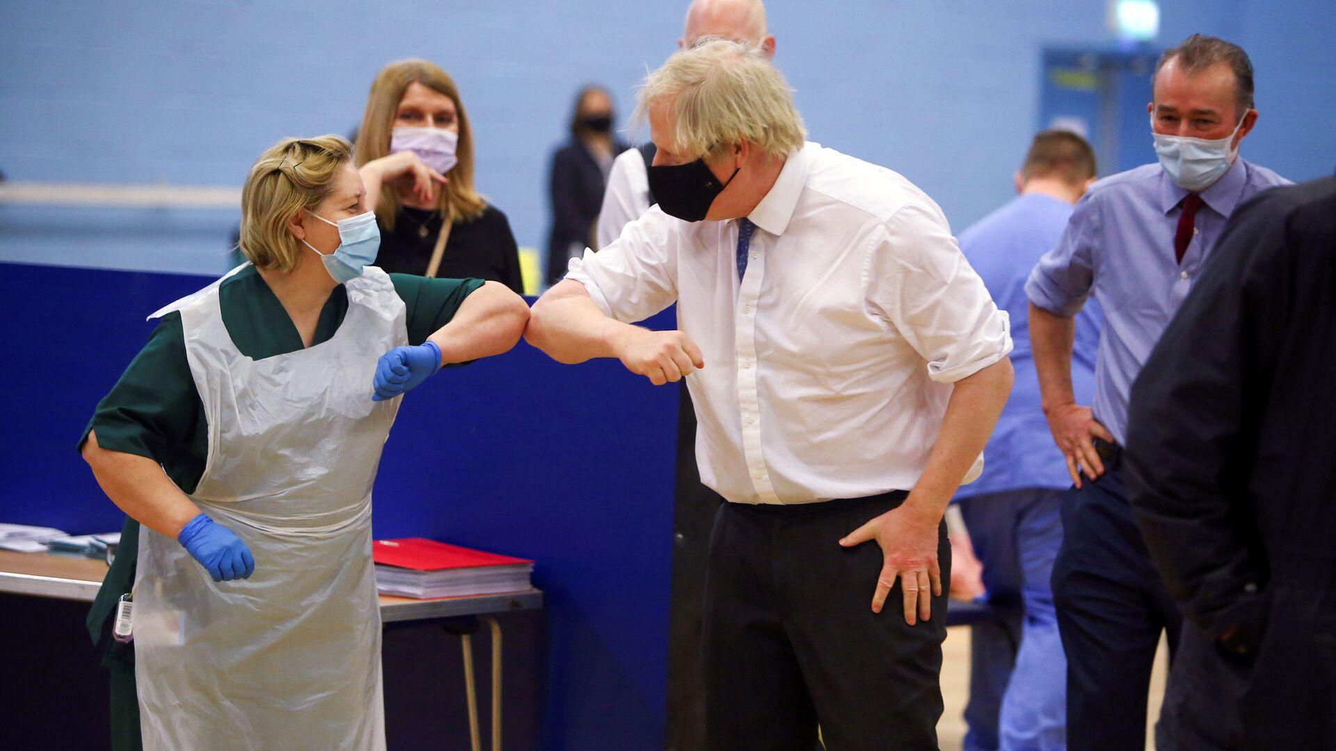 Премьер-министр Великобритании Борис Джонсон с медсестрой во время посещения центра вакцинации от коронавируса в Кумбране - Sputnik Italia, 1920, 06.07.2021