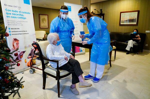 Le infermiere di una casa di riposo in Spagna con una paziente anziana che si prepara per farsi vaccinare.  - Sputnik Italia