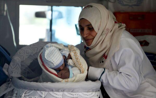 Infermiera con due gemelli siamesi in ambulanza presso l'aeroporto di Sana'a, Yemen. - Sputnik Italia
