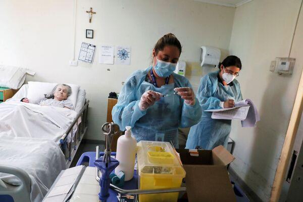 Le operatrici sanitarie in una casa di riposo a Santiago, Chile, stanno per somministrare il vaccino anti-Covid a una paziente anziana.  - Sputnik Italia