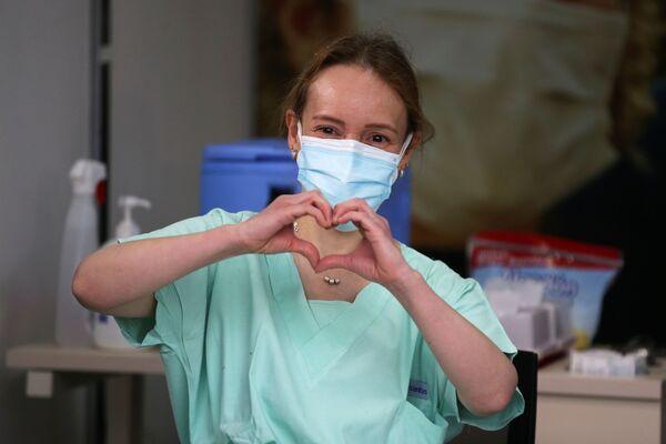 La dottoressa Silvia Alejandra Gelvez, medico d'emergenza-urgenza presso la Colombia Clinic, fa il gesto del cuore prima di ricevere un'iniezione con la dose del vaccino Pfizer-BioNTech, Bogotà, Colombia, il 18 febbraio 2021. - Sputnik Italia