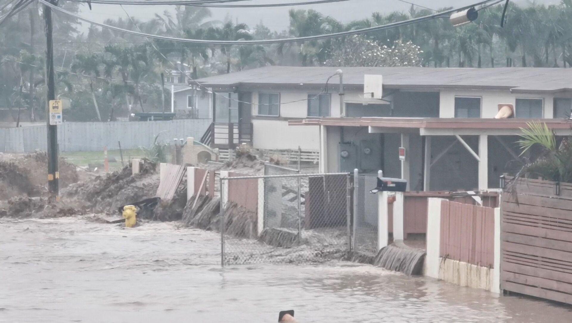 Social media video grab shows floodwaters streaming down a street in Hauula, Hawaii - Sputnik Italia, 1920, 11.03.2021