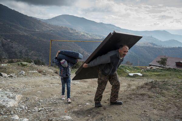 Murad Mvrgaryan e suo figlio Vahak portano le cose fuori dalla loro casa prima di lasciare la città di Lachin - Sputnik Italia